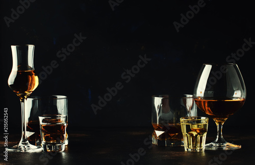 Spoed Foto op Canvas Bar Set of strong alcoholic drinks in glasses and shot glass in assortent: vodka, rum, cognac, tequila, brandy and whiskey. Dark vintage background, selective focus