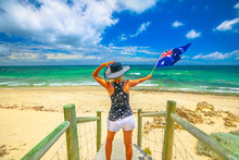 Woman On The Sand Looking At The Turquoise Sea Waving Australian Flag. Mettams Pool In Trigg Beach, North Beach Neighborhood Near Perth, Western Australia. Tourism In Oceania.