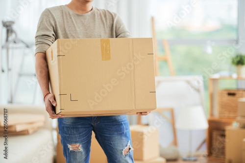 Obraz Crop view of strong male in casual clothes carrying large cardboard box on moving day with cartons and drawing easels on blurred background of art workshop. - fototapety do salonu