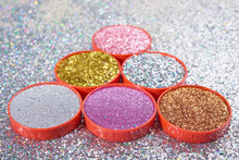 Close-up Shot Of Colorful Gold Pink And Silver Glitters Composed In Piles In Small Lids On Silver Shiny Surface