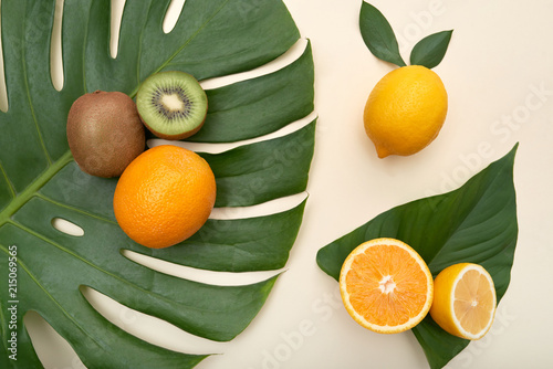 Fotografie, Obraz  Top view of oranges and lemons with kiwi composed on green Monstera leaves on wh