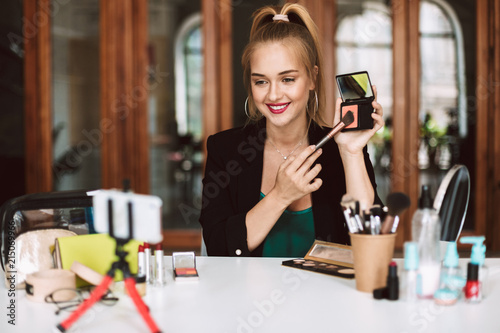 Fotografía  Beautiful beauty blogger happily showing how to make up while recording new vide