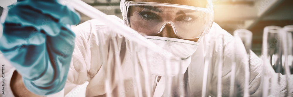 Fototapety, obrazy: Close up of a protected science student dropping liquid in a