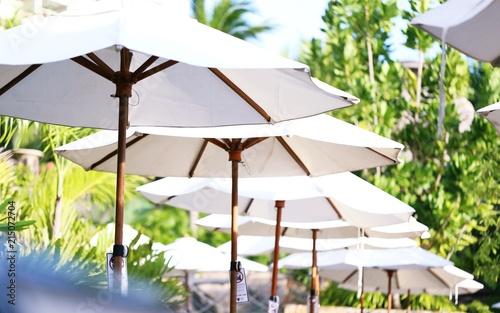White fabric of beach and swimming pool umbrellas closeup ...