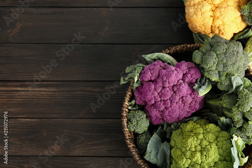 Wicker basket with different cabbages on wooden table, top view. Healthy food