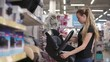 Attractive young woman is choosing new carriage for her child. Woman shopping in supermarket for baby things. Good high-quality black carriage.