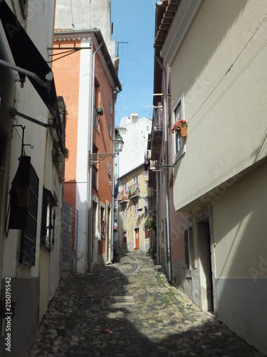 Deurstickers Smal steegje View of a narrow cobbled uphill street in Lisbon