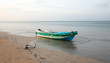 Small fishing boat anchored on Nilaveli beach at sunset in Sri Lanka Asia