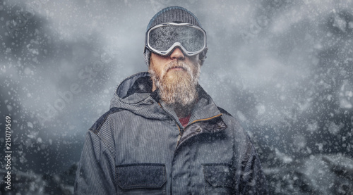 Poster Glisse hiver Portrait of a redhead snowboarder with a full beard in a winter hat and protective glasses dressed in a snowboarding coat posing at a studio, looking away.