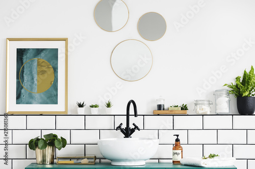 Fotografía Poster next to round mirrors above washbasin and plant in white bathroom interior