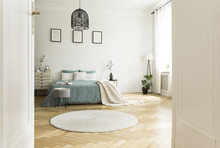 White Round Rug In Spacious Bedroom Interior With Green Bed Under Lamp And Posters. Real Photo