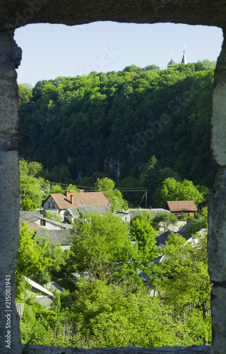 Fotografie, Obraz  View from old window to village against canyon