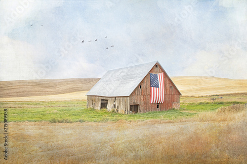 Textured photograph of an old red rickety barn with an American flag on the side Fotobehang