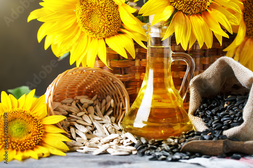Fototapeta Closeup photo of sunflowers and sunflower oil with seeds on on a wooden table. Bio and organic concept of the product. obraz