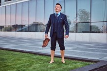 Confident Businessman Dressed In Elegant Suit Holds His Shoes Enjoying While Standing Barefoot On A Green Lawn Against Cityscape Background.