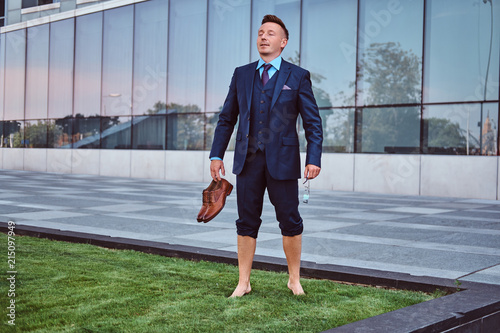 Confident businessman dressed in elegant suit holds his shoes enjoying while standing barefoot on a green lawn against cityscape background Wallpaper Mural