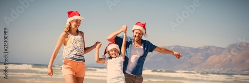 Fotografia  Happy family wearing Santa hat while enjoying at beach