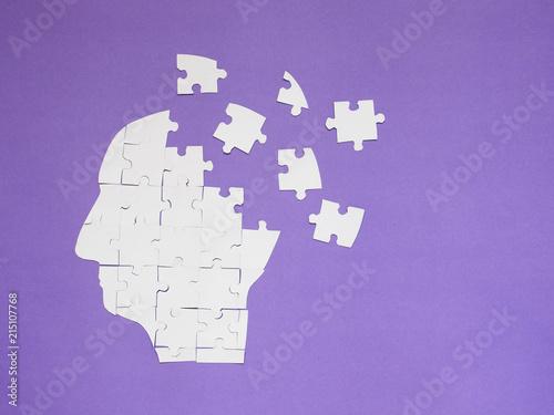 Obraz na płótnie White jigsaw puzzle as a human brain on purple background w/ copy space