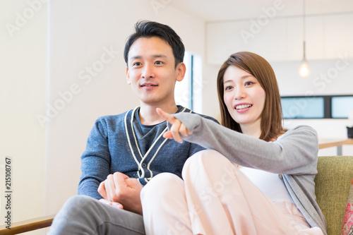 Fotografía  会話しながら同じ画面を見るカップル(ホームシアター・テレビ・映画)