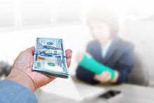 Hand Holding American Dollar Currency Isolated On Blurred Blackground Injured Woman With Broken Hand And Green Cast On Arm, Insurance Health Concept.