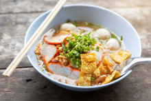 Close-up Of Thai Noodle Soup With Meat In White Bowl On Wooden Background.