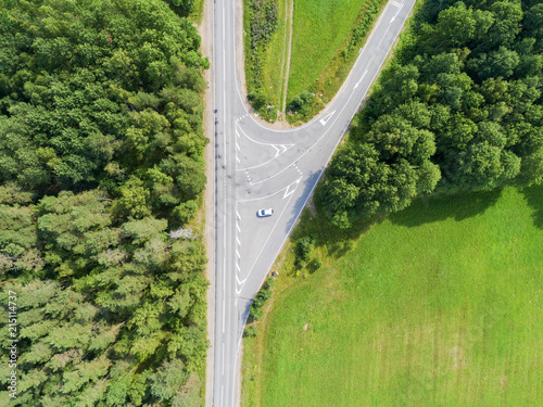 Fototapeta Aerial view of highway. Aerial view of a country road with moving car. Car passing by. Aerial road. Aerial view flying. Captured from above with a drone. obraz na płótnie