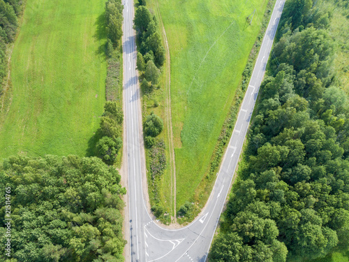 Fototapeta Aerial view of highway. Aerial view of a country road. Car passing by. Aerial road. Aerial view flying. Captured from above with a drone. obraz na płótnie