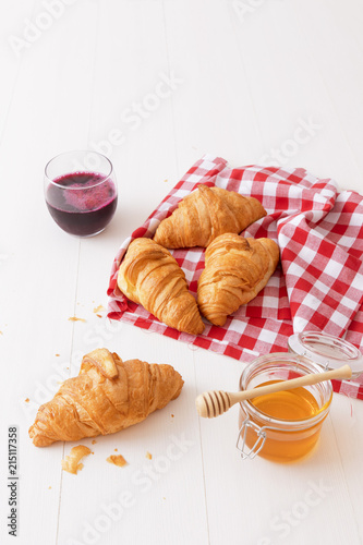 Foto op Aluminium Buffet, Bar French style breakfast, a white wooden table with glass of fresh beetroot smoothie, croissants and glass bowl of honey, few croissants placed on the red and white french checkered fabric.