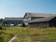 Two-storey Wooden Apartment Houses With A Wooden Extension On A Rural Street In A Village In Russia