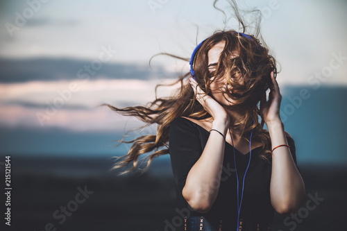 Obraz na płótnie portrait of a beautiful girl in headphones listening to music on nature
