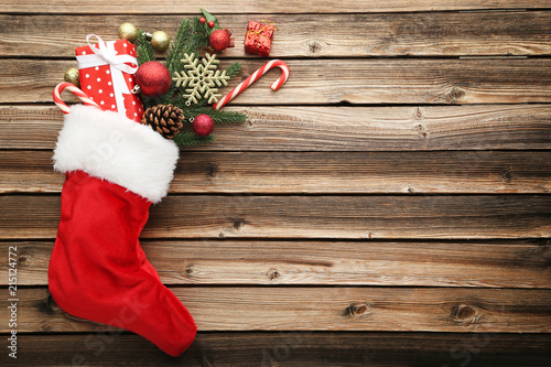 Valokuva Red stocking with fir-tree branches and christmas decorations on wooden table