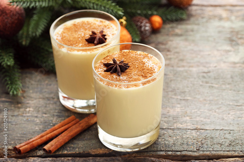 Staande foto Cocktail Eggnog in glasses with cinnamon and star anise on wooden table