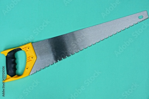 Fotografie, Obraz  A hacksaw on wood with a yellow handle on a green background