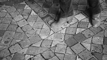 Castle Visiting. Closeup Of Young Woman Legs In Motion On Terracotta Tile Floor. Sightseeing Background. Black And White Photo.