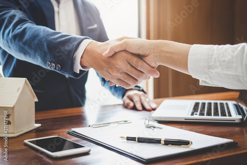 Fototapeta  Real estate agent and customers shaking hands together celebrating finished cont
