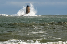 Great Waves Cover Stone Lighthouse Tower In Maine