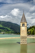 In 1950 The Old Village Of Curon Venosta - Graun Im Vinschgau, Trentino Alto Adige - South Tyrol, Italy, Was Abandoned And Rebuilt Later On The New Shores As The Local Valley Was Dammed In Order To Produce Hydro-electricity. The Half-submerged Bell Tower Of The Old Village Has Become A Landmark Since Then And Today Has Become A Popular Tourist Attraction.