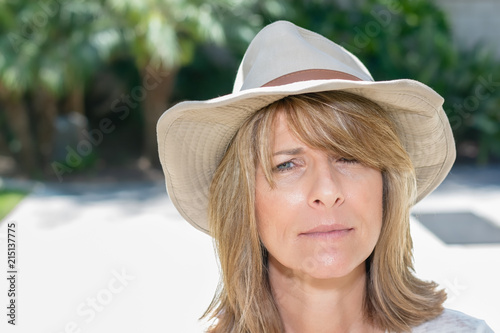 Beautiful woman wearing cowboy hat on patio in bright sunshine - Buy ... 9d0fc0402c87
