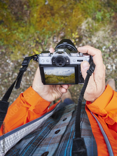 High angle view of man reviewing beautiful nature photograph on digital camera