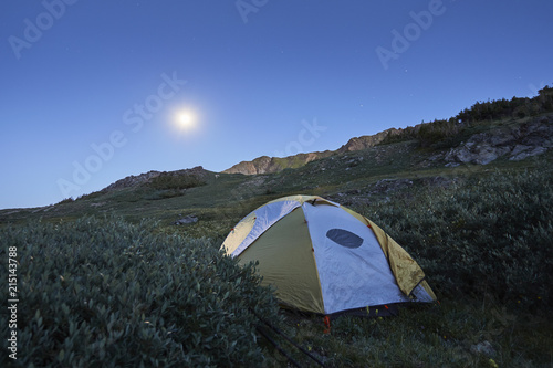 Tent on grassy field against clear blue sky at dusk