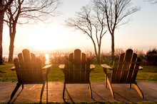 A Row Of Adirondack Chairs At Sunset