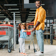 smiling african american man standing with daughter near shopping trolley in supermarket