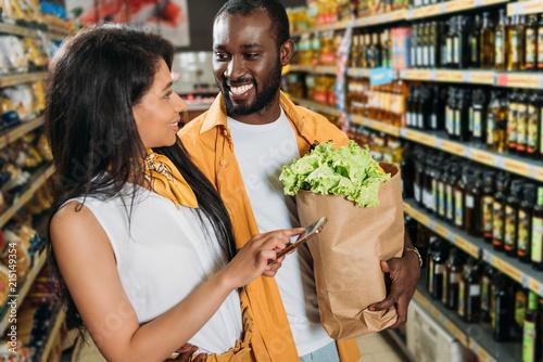 Plakat młoda para african american z smartphone i papierową torbę z jedzeniem w supermarkecie