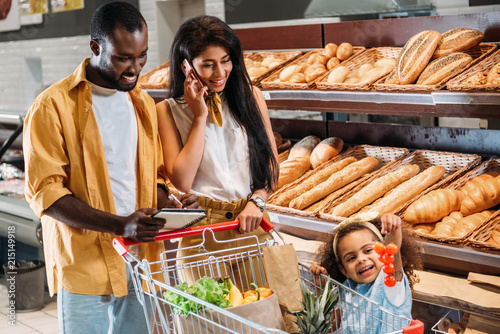 Deurstickers Bakkerij african american woman talking on smartphone while her husband and daughter standing near with shopping trolley in supermarket