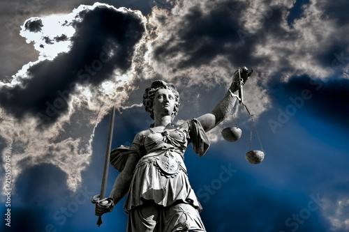Fotografía  Die Gerechtigkeitsgöttin Justitia vor einem dramatischen Himmel mit Waagschale i