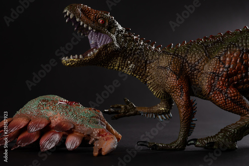 Carcharodontosaurus with a stegosaurus body nearby on dark background close up