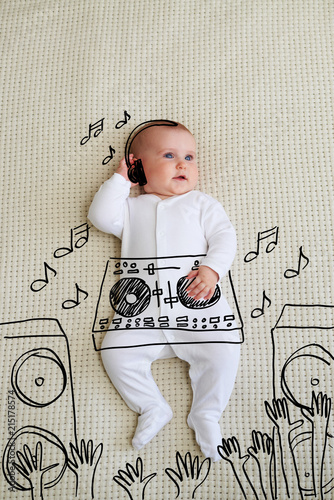 Obraz Cute DJ baby girl wearing headphones playing music at mixer - fototapety do salonu