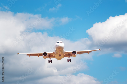 Tuinposter Vliegtuig plane at landing on blue sky background with white clouds. Airplane turbine and wing view