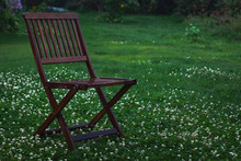 Wet Wooden Brown Chair On Gras...