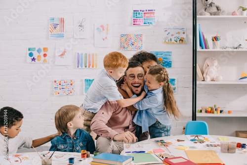 Fotografie, Obraz interracial kids hugging happy teacher at table in classroom
